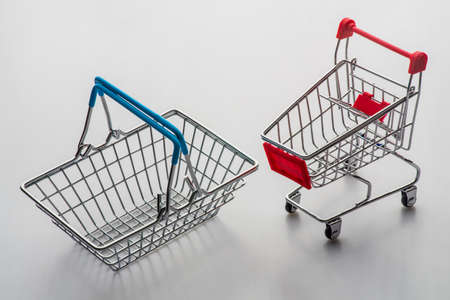 Empty grocery shopping cart and basket. Isolated over white background. Zdjęcie Seryjne
