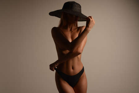 Beautiful young woman in a hat posing in the studio. - image
