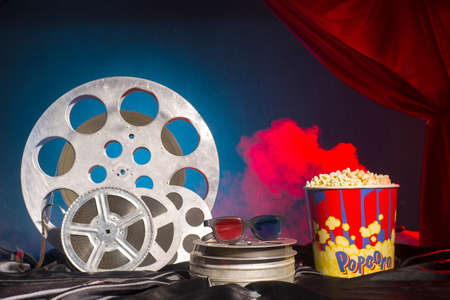 Old film reels, popcorn and 3d glasses on the table. Focus on glasses. Multicolored background. Evolution Film Media 写真素材