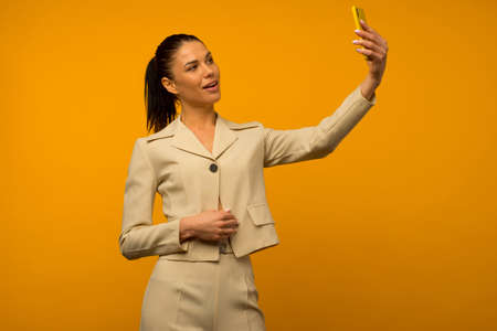 Young girl with facial skin problems posing with a smartphone on a yellow background. Foto de archivo