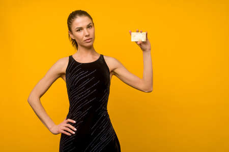 Young girl with facial skin problems posing with a smartphone on a yellow background. Zdjęcie Seryjne