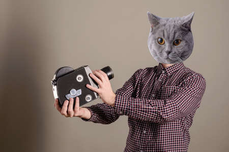Collage of young attractive cameraman in a plaid shirt and a cat head takes himself off to an old movie camera.