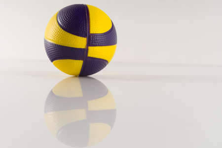 Basketball ball with yellow and purple spots on a white background. Antistress ball