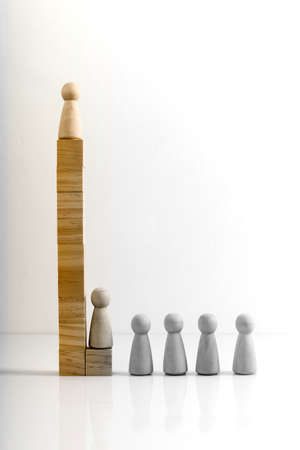 Wooden figures stand on the cubes that represent the stairs. The concept of social inequality or career growth.