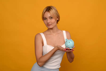 Beautiful young girl holding a pig piggy bank on yellow background. For saving money wealth and financial concept.- image
