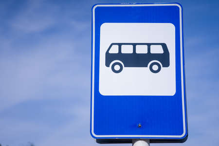 Blue and white bus stop sign in Europe with sky background. Zdjęcie Seryjne