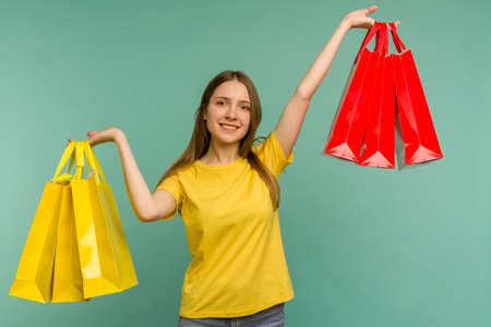 Photo of nice charming girl attractive joyful girl having just ended up shopping and being overjoyed and cheerful while isolated with blue background - image