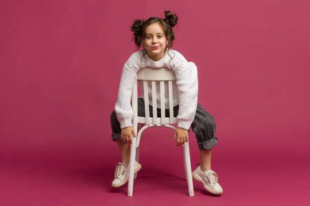 Photo of smiling little girl child isolated over pink background. Looking camera. Zdjęcie Seryjne