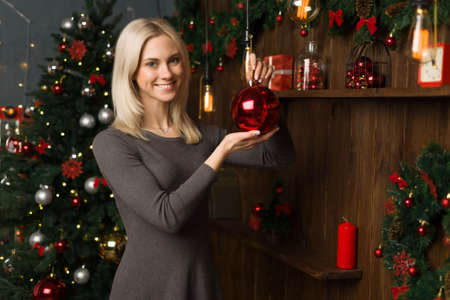 Beautiful young woman decorates a Christmas tree with balls in the New Year home interior. - image