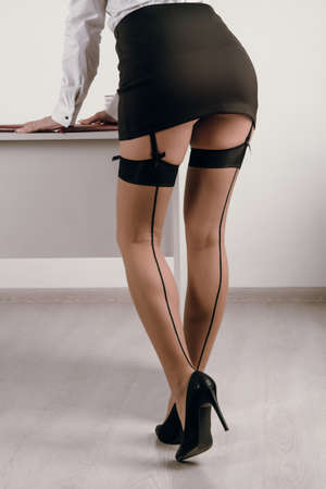 Provocative young woman with long legs in office.