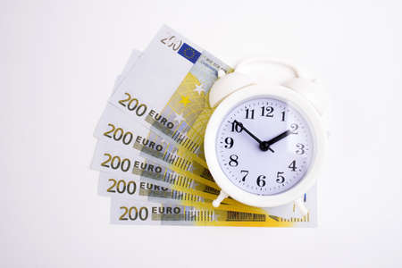 Retro styled alarm clock euro cash isolated on white. Time is money concept