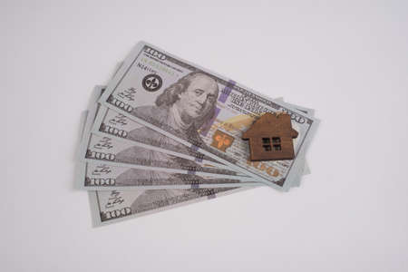 Toy house on American dollar bills on a white background.