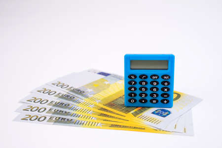 Blue calculator and dollars on a white background. 免版税图像