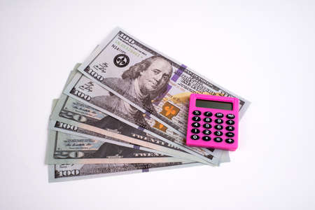 Pink calculator and dollars on a white background. 免版税图像