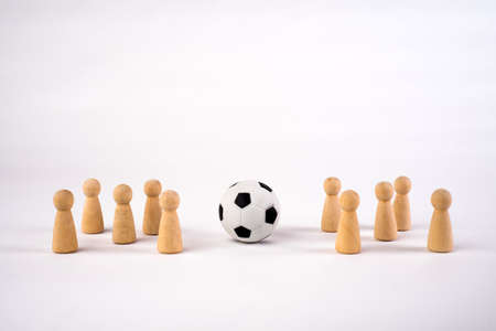 Two teams of football players. Wooden pawn and soccer ball on a white background.