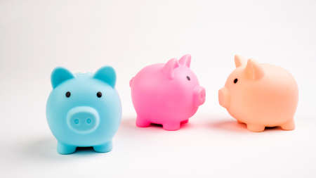 Growing investment - three piggy banks different color isolated on white
