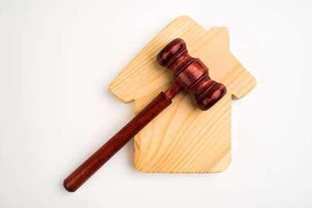 Miniature wooden house and judge's hammer. The concept of resolving property disputes. Property alienation. Confiscated housing. Nationalization. Services of a lawyer. Court. Gavel. Law 免版税图像