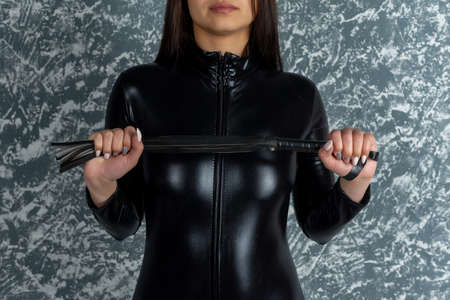 Beautiful woman mistress in latex bodisyut stands back holding a whip Stock Photo