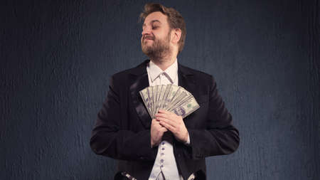 Positive butler man in a tailcoat hold money.