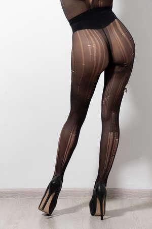 Fine female legs in pantyhose in a fishnet. Sexy woman ass.