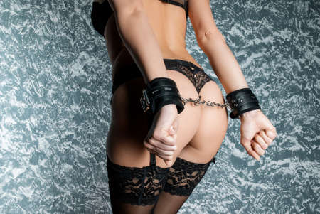 Beautiful woman in in panties and handcuffs stands with her back in set. Adult game