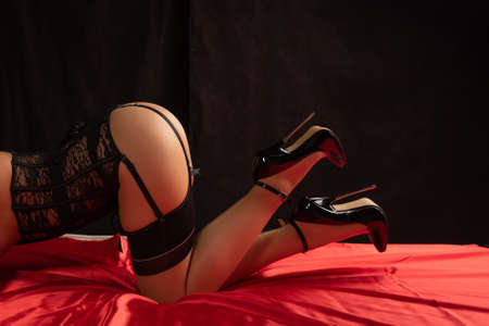 Young adult female in vintage stockings, corset, and high heels on red bedsheet