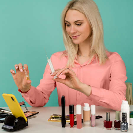 A beautiful girl blogger shows a syringe and an ampoule with an anti-aging drug in her hand. Leads online on a smartphone in social networks. Close-up portrait of a vlogger woman on a blue background.