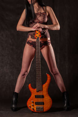 Beautiful high glamour fashion model in lingerie with a bass guitar on dark background