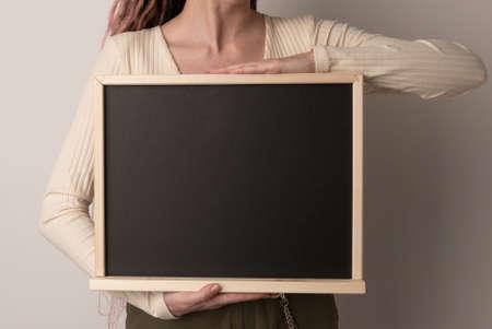 beautiful woman holding chalk blackboard on white background