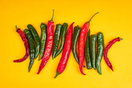 Red and green hot chili peppers on yellow background