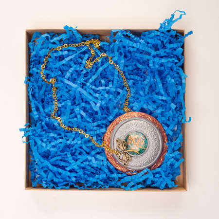 jewelry for the neck lies in a box with shavings