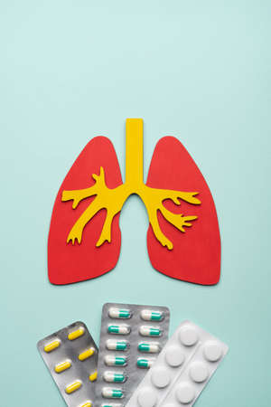 lungs and a pils on a blue background. concept of respiratory disease, pneumonia, tuberculosis, bronchitis, asthma, lung abscess 免版税图像