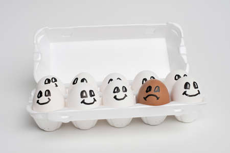 tray full of smile white eggs and only one different sad orange egg. Discrimination, Xenophobic, racist concept.
