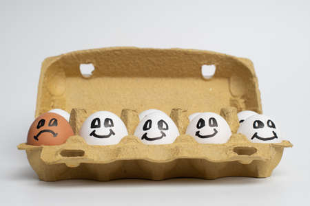Paper tray full of smile white eggs and only one different sad orange egg. Discrimination, Xenophobic, racist concept.