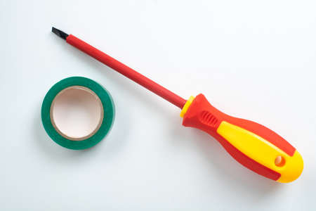 Red plastic dielectric screwdriver for electrical work with insulated tip and green insulating tape
