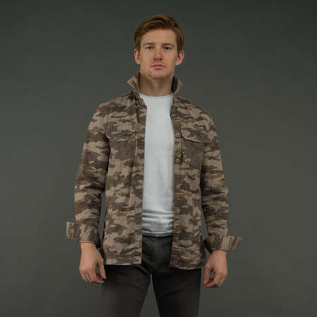 Handsome man wear military jacket on gray background