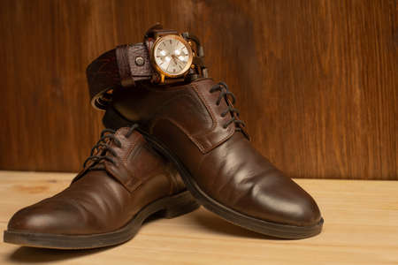 Men's accessories with brown leather belt, shoes and watch on wooden background 免版税图像