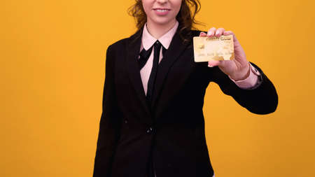 business woman standing isolated over yellow background, holding credit card