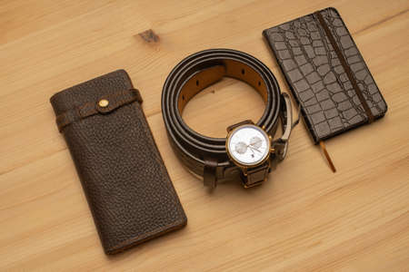 Men's accessories with brown leather wallet, belt, notebook and watch on wooden background 免版税图像