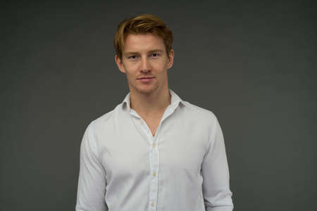 Red-haired young man with problem skin on the background.