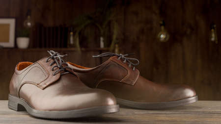 Fashionable men's classic brown shoes on a wooden background.