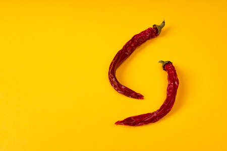 Red dry hot chili peppers on yellow background.