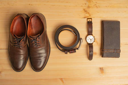 Men's accessories with brown leather wallet, belt, shoes and watch on wooden background