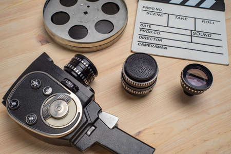 Movie clapper, film reel and camera on wooden background, top view