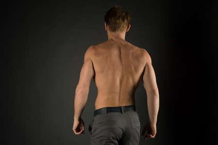 strong athletic man back on black background Standard-Bild
