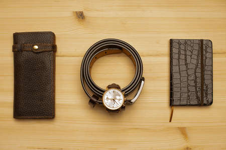 Men's accessories with brown leather wallet, belt, notebook and watch on wooden background Standard-Bild