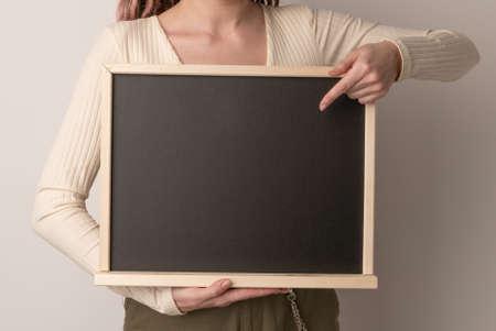 beautiful woman pointing on blank chalk blackboard on white background
