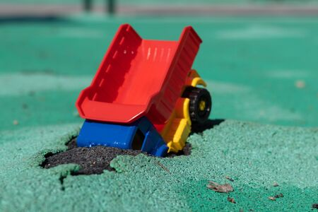 The car fell into the pit. Toy plastic truck with a red body had an accident. Hole on Asphalt Coating. The road needs repairs. Accident has occurred.
