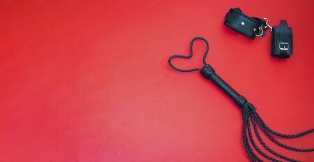 Accessories for bdsm on a red leather background. Lash in the shape of a heart and leather handcuffs. Erotic shop. Valentine's Day. Copy space. Foto de archivo