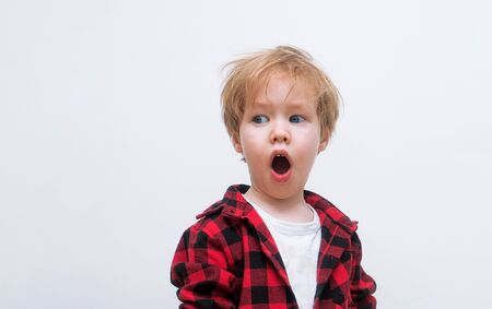 European blond child opened his mouth and is surprised. Kid is looking toward free space. The hipster boy woke up in shock and it was time for him to get a haircut. White background Stock Photo